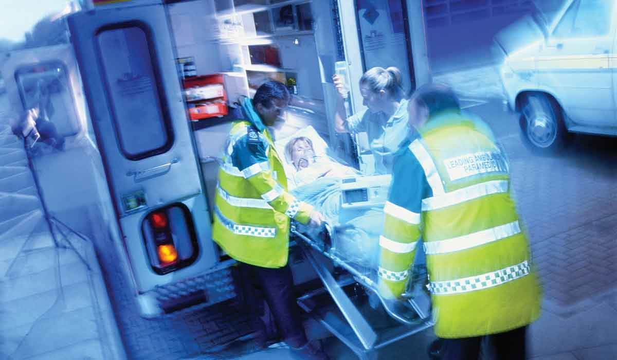 Three EMTs lead a stretcher into the back of an ambulance