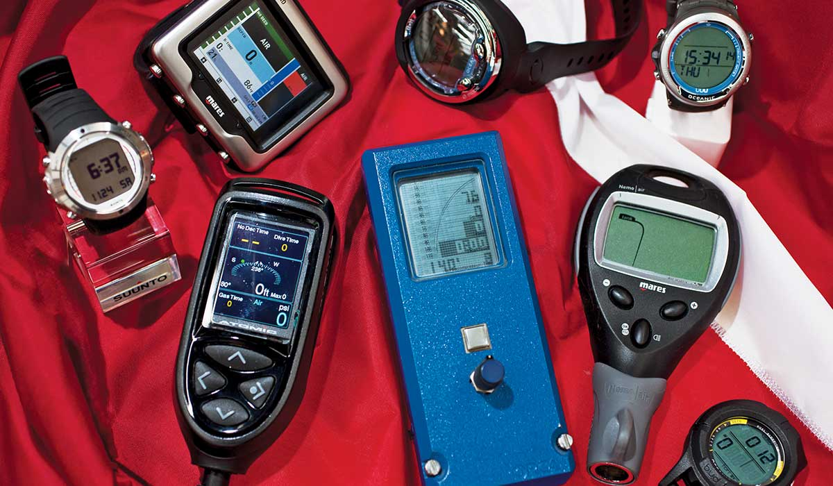 Variety of dive computers and watches on a red fabric