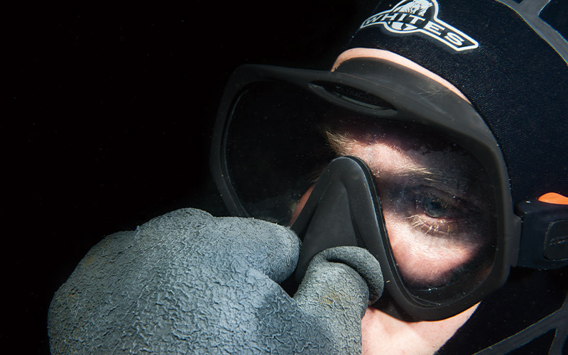 Diver plugs his nose while wearing mask