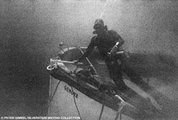Old grainy image of a diver next to a sunken dive boat