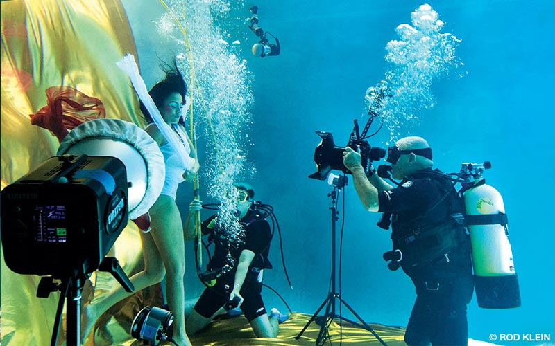 A scuba diving photographer is behind the camera shooting a model who is holding her breath
