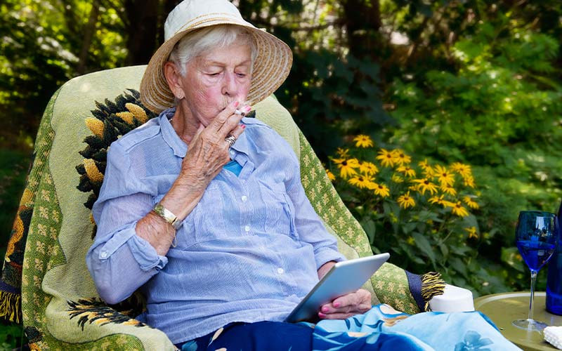 Old woman in a straw hat is smoking a cigarette in her garden