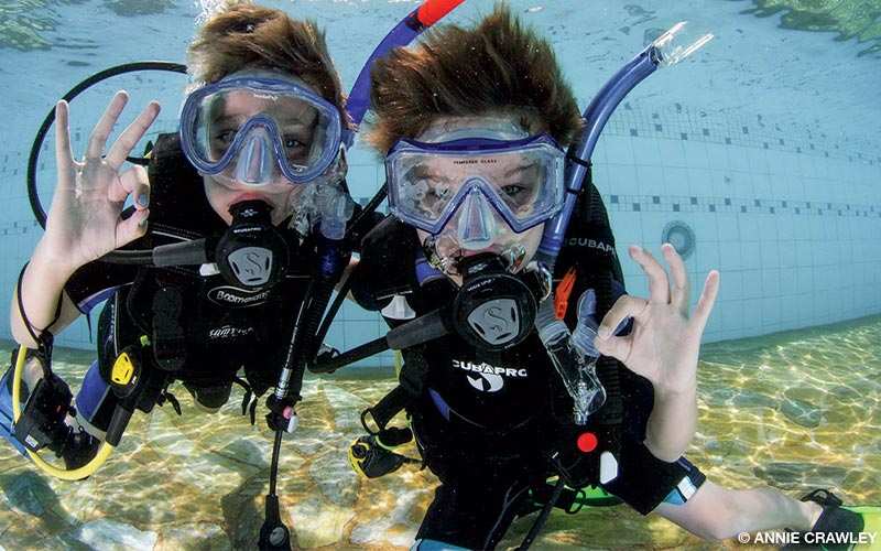 Two young divers have fun working on their buoyancy control and demonstrating hand signals.