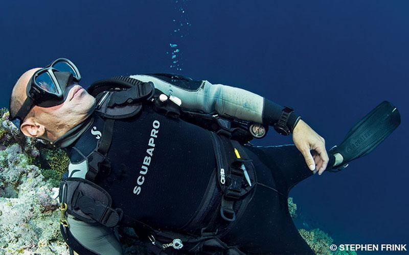 An unconscious diver floats near coral