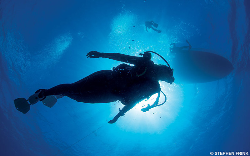 Woman dives beneath a boat