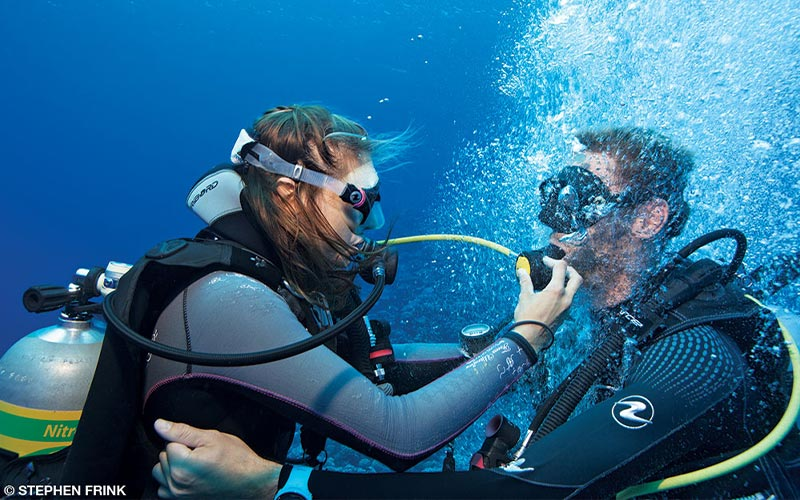 A female dive buddy gives her dive buddy the regulator so he can get air