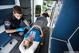 A male EMT treats a female patient. They are in an ambulance.