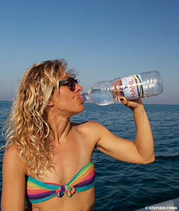 A woman in a bikini drinks from a large bottle of water