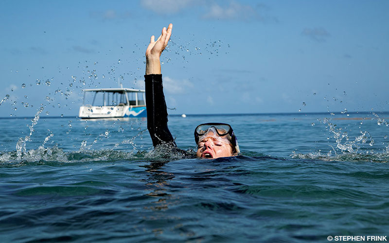 A female diver breaks the surface of the water. She's in shock and looks like she is in trouble.