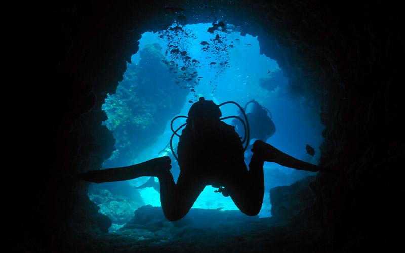 In a stock image, a diver swims through a cave. Another diver is in the background