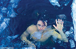 A shirtless man is underwater and looks terrified.
