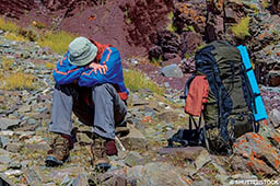 A hiker sits down because he has altitude sickness and is uncomfortable.