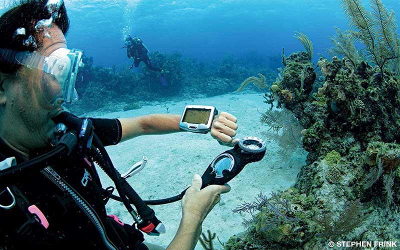 Diver checks dive computer strapped onto left arm