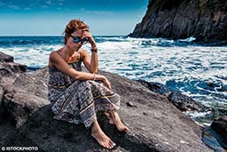 A woman sits on a rock and is worried. She has anxiety.