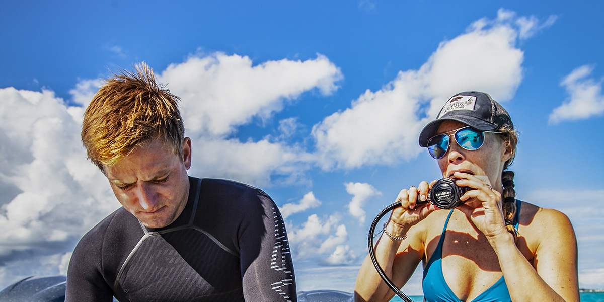 a male and female diver check their regulator and other equipment as they prepare to dive