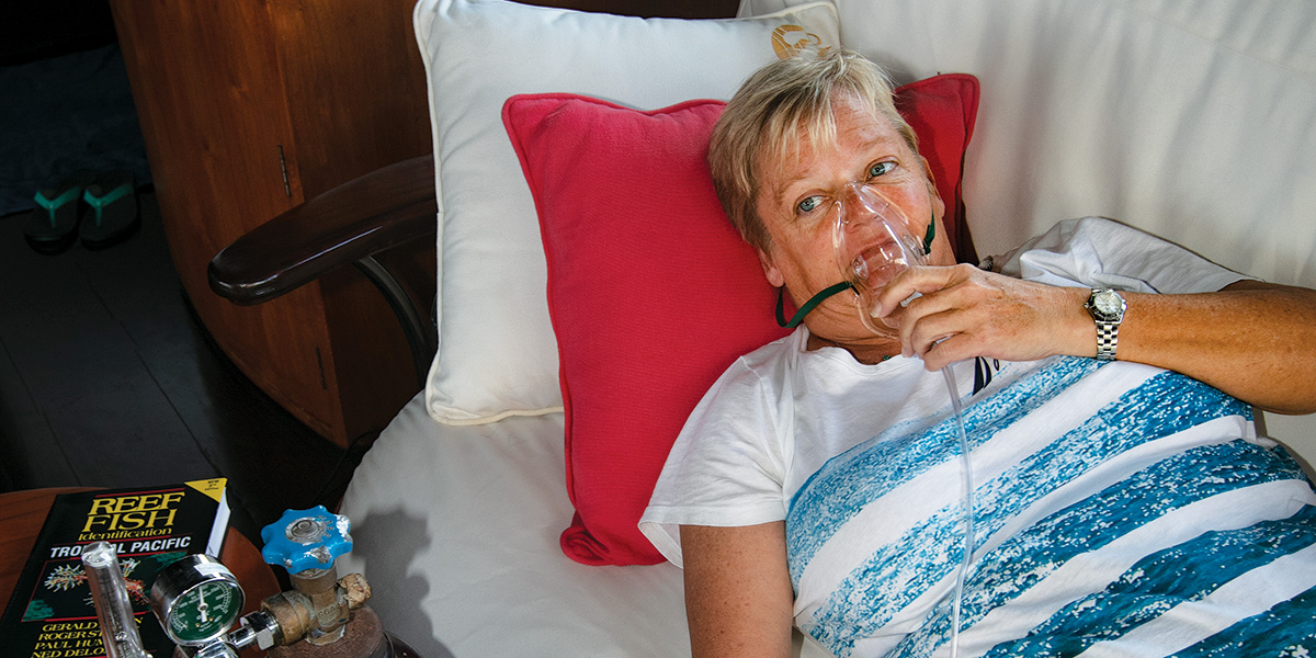 woman breathes oxygen in a reclined position