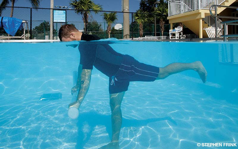 A man performs the Aqua Warrior 3 exercise using a pool noodle in a swimming pool.
