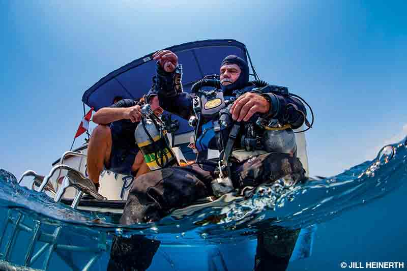 A man on a boat helps a diver with a scuba cylinder before the diver enters the water.