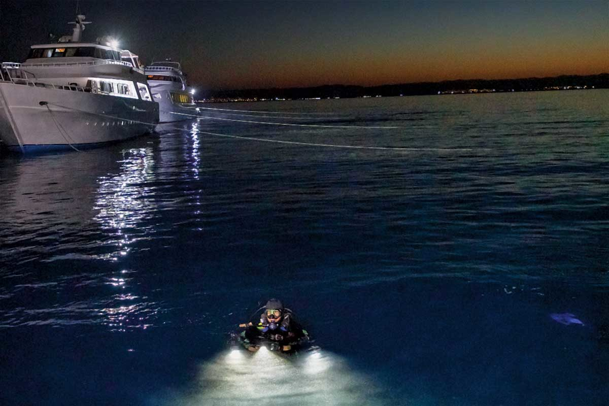 A diver is in the water at the surface at dusk as a liveaboard waits nearby.