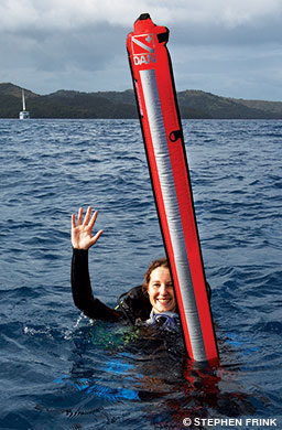 A female diver with a deployed surface marker buoy waves at the surface.
