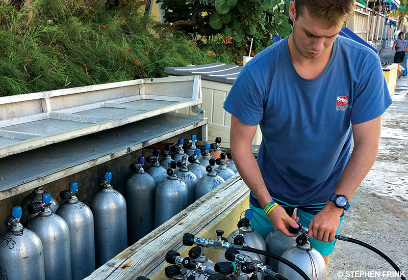 Young man in blue shirt fills scuba cylinders.