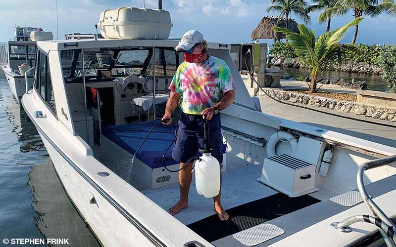 A man sprays disinfectant on boat surfaces