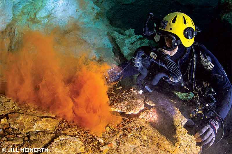 A diver watches dust rise from layers of rock underwater in a cave in the Bahamas.