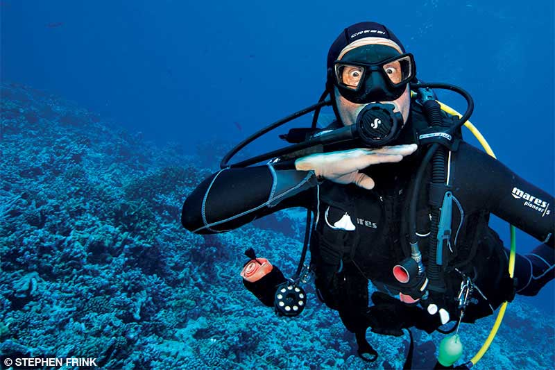 A diver underwater gives an out of air signal by putting his hand across his throat.
