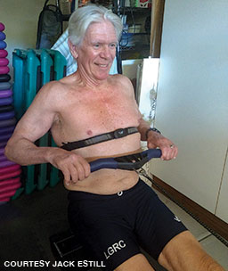 A shirtless older man exercises on an indoor rower while wearing a heart monitor.