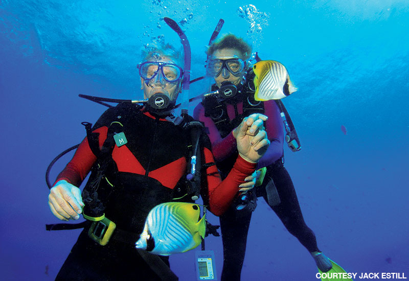 Male and female diver in red and black wetsuits pose for a photo underwater before descending