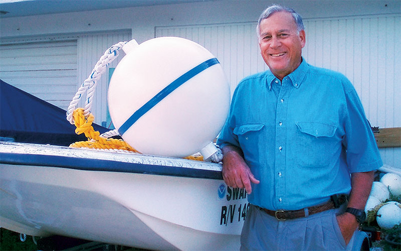 A man in a blue shirt, John Halas, stands next to a boat with a mooring buoy on top.