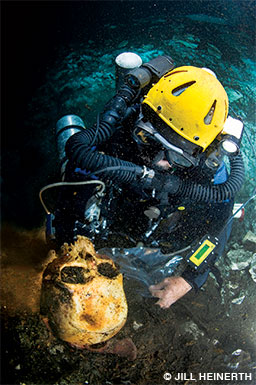 Kakuk in his dive gear lifts an ancient skull to examine it.
