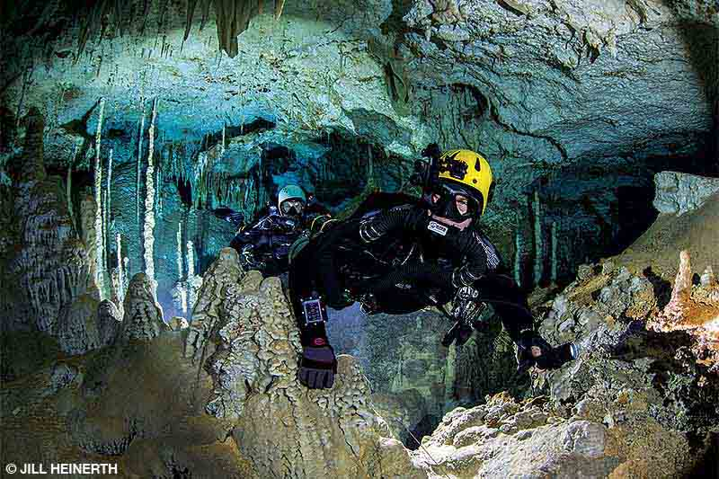 Two divers swim through a cave.