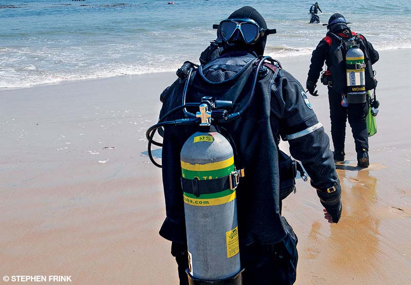 Divers geared up make their way from the shore to the water.