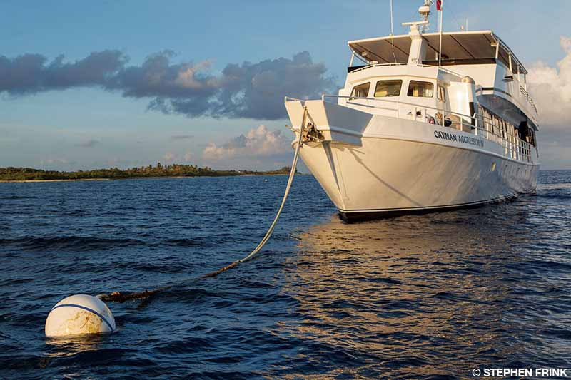 A liveaboard boat is tied to a mooring buoy in open water.