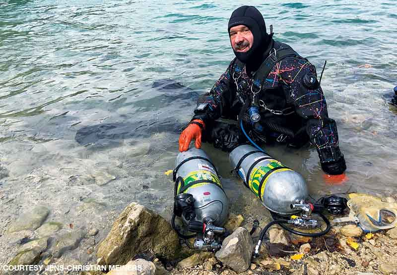 Meiners in a drysuit sits in the water near shore after a dive with two nitrox tanks