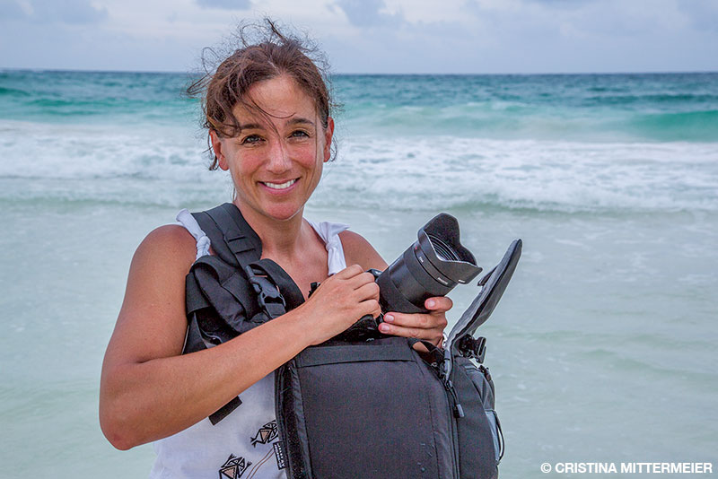 Cristina Mittermeier on the beach with her camera gear
