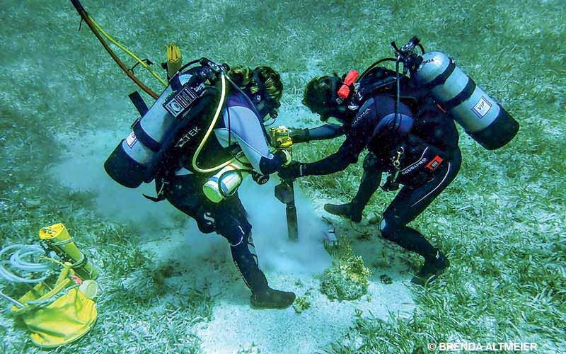 Divers drill seafloor to install a mooring buoy system