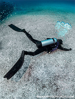 A diver tries holds onto a tiny ridge of old lava flow to prevent an uncontrolled ascent.