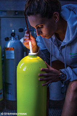 Woman uses a light to visually inspect a cylinder.