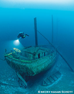 A technical diver illuminates the wheel on the stern of the Cornelia B. Windiate shipwreck.