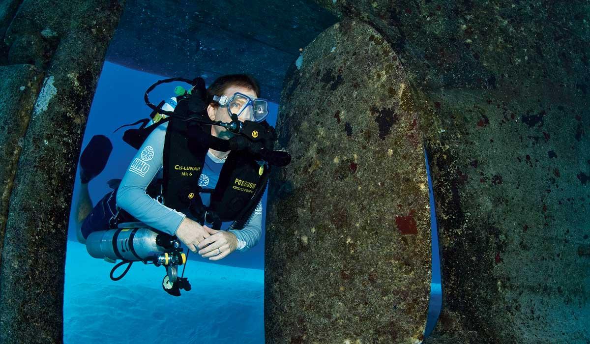 A tech diver floats through a wreck