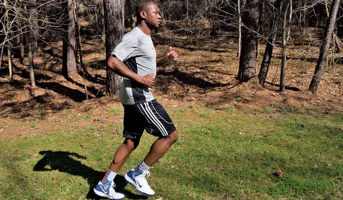 Male, Black, personal trainer jogs in place on the grass