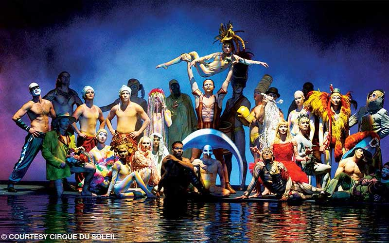 A group of performers in colorful costumes pose as a group next to water
