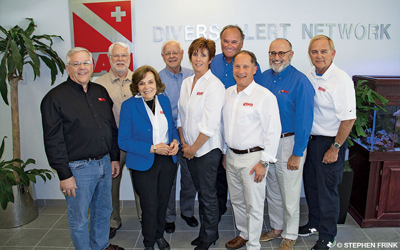 Seven men and two women pose in DAN headquarters. They are the DAN Board of Directors.