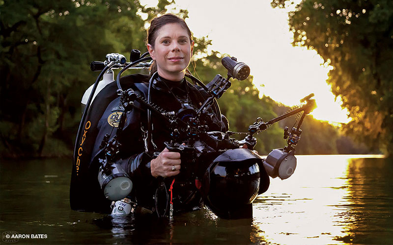 Diver Jennifer Idol wears her scuba suit and holds a camera