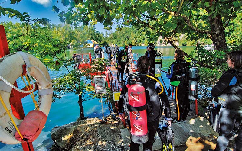 Divers line up on dock outsite quarry waiting to get in to dive
