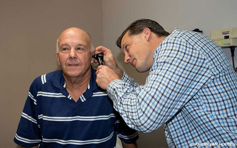 A doctor in a blue plaid shirt, examines the left ear of a bald man