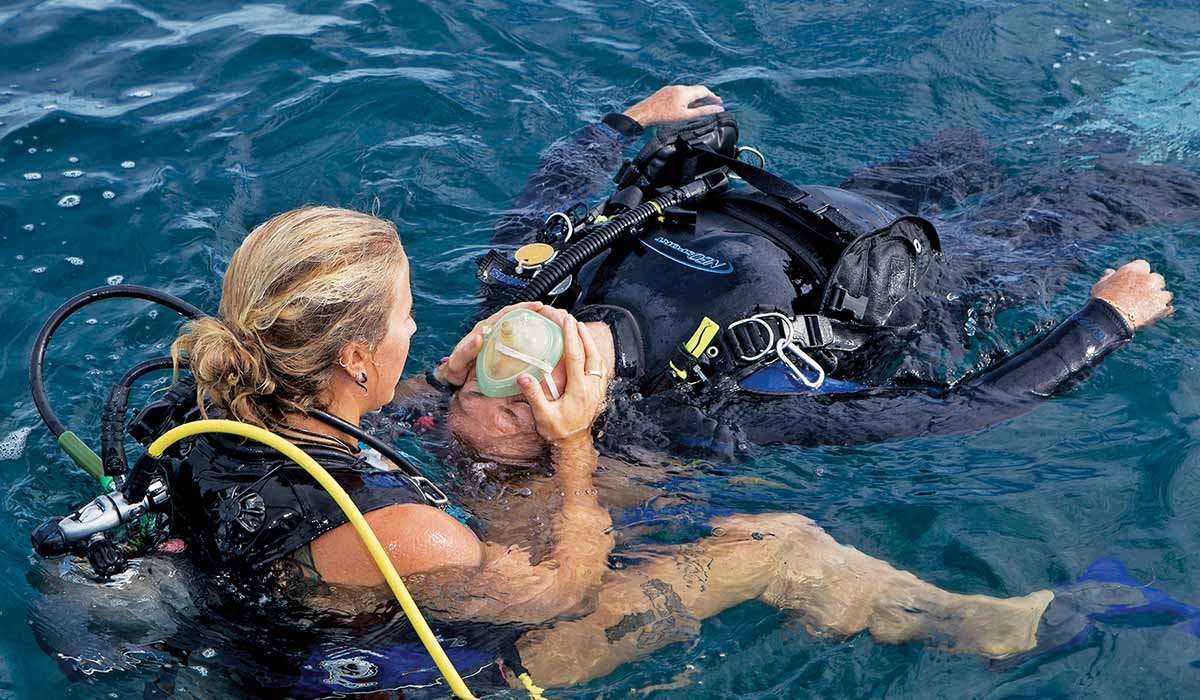 Female diver helps another diver in the water
