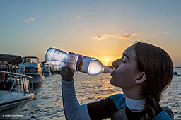 Female person drinks from a water bottle at sunset
